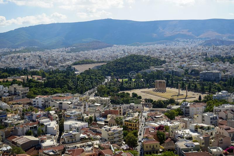 Vista panorâmica da cidade bonita de Atenas da acrópole que vê a ruína antiga, arquitetura de construção, rua urbana, árvores, mo fotos de stock royalty free