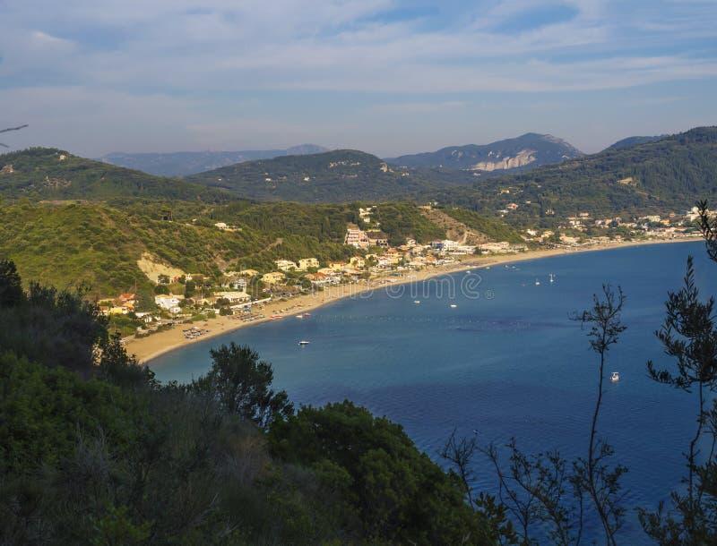 Vista panorâmica da praia da areia de Agios Georgios Pagon com montes verdes e navios de navigação na ilha de Corfu, Grécia, céu  fotografia de stock