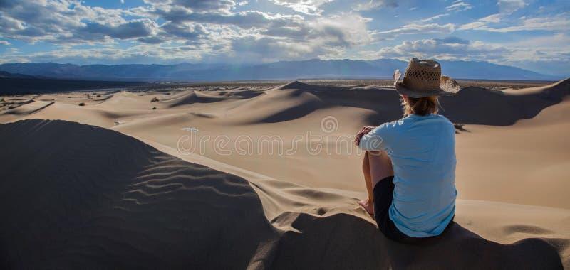 Vista panorâmica das dunas de areia lisas do Mesquite no parque nacional de Vale da Morte com a fêmea no chapéu que olha a vista imagens de stock