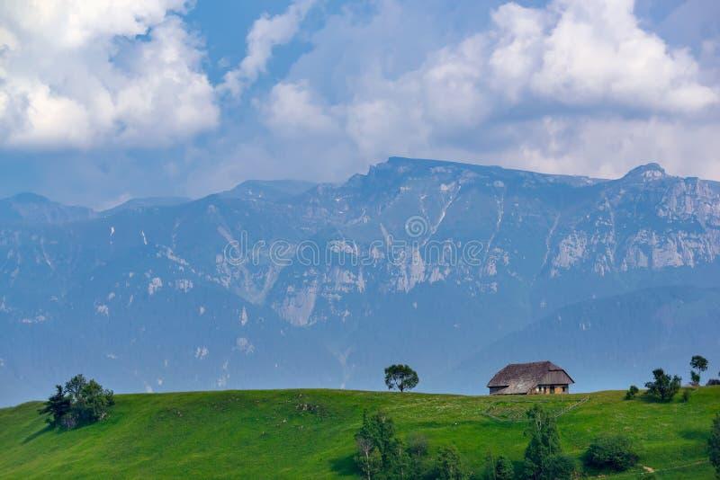 Vista panorâmica de uma paisagem da mola nas montanhas, com uma casa do sheepfold nos picos, nas árvores dispersadas e nas montan imagens de stock