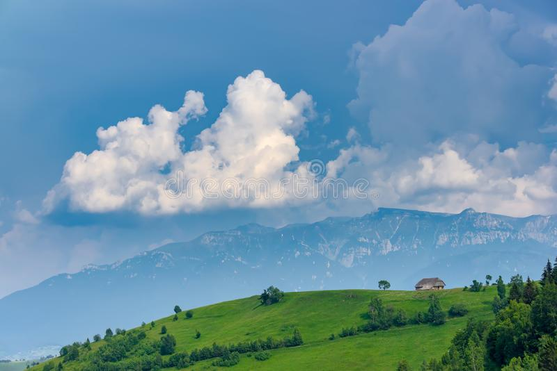 Vista panorâmica de uma paisagem da mola nas montanhas, com uma casa do sheepfold nos picos, nas árvores dispersadas e nas montan fotografia de stock