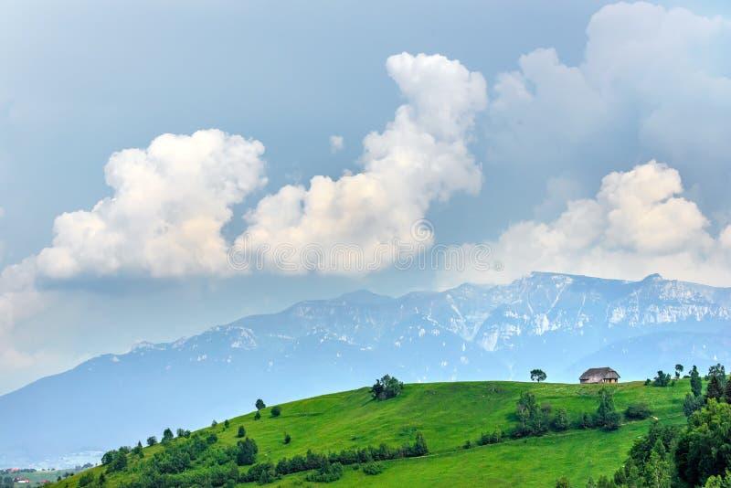 Vista panorâmica de uma paisagem da mola nas montanhas, com uma casa do sheepfold nos picos, nas árvores dispersadas e nas montan fotos de stock