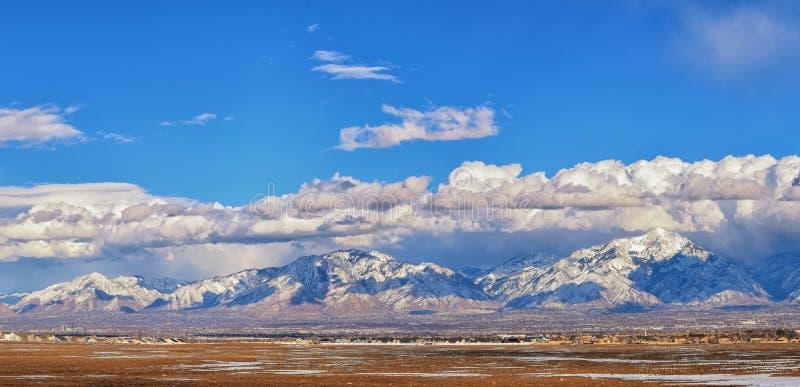 A vista panorâmica do inverno da neve tampou Wasatch Front Rocky Mountains, vale de Great Salt Lake e Cloudscape de Bacchus Highw fotografia de stock royalty free