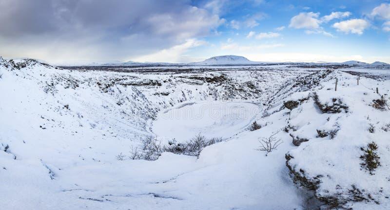 Vista panorâmica do Kerid Volcano Iceland com neve e gelo no lago vulcânico da cratera no inverno sob um céu azul foto de stock