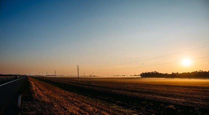 Vista panorâmica do nascer do sol sobre os campos que cultivam na névoa e na estrada asfaltada fotografia de stock