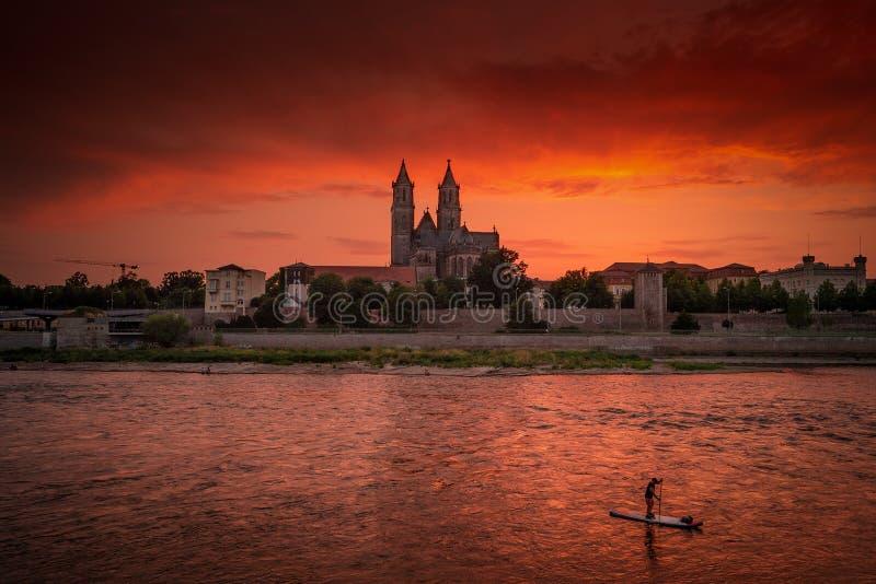 Vista panorâmica do por do sol ensanguentado na frente da catedral em Magdeburgo, em rio Elbe e em um paddler só, Alemanha fotos de stock royalty free