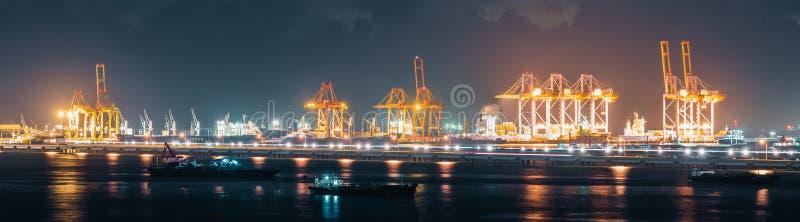 Vista panorâmica dos guindastes que carregam recipientes da expedição no porto de transporte da carga na noite, tamanho da bandei foto de stock