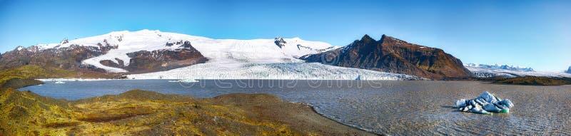 Vista panorâmica dos iceberg de derretimento que flutuam no lago glacial Fjallsarlon com parto da geleira de Fjallsjokull na lago fotografia de stock