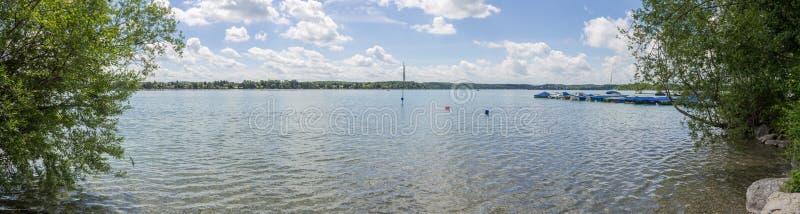 Vista panorâmica no lago bonito Wörthsee tomado do beira-mar paisagem Verde-azul com bandeira, barcos, cais e plantas na fotos de stock royalty free