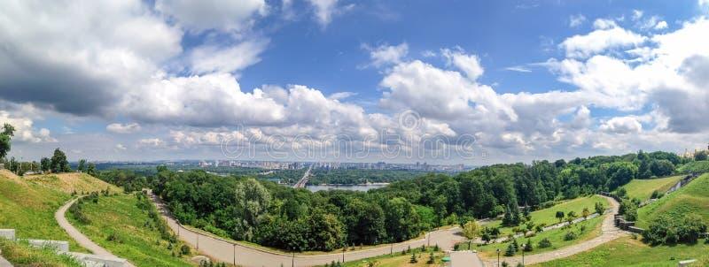 Vista panoramica dall'area del parco agli alberi, all'erba, al cielo nuvoloso, al fiume di Dnieper ed alla città di Kiev, Ucraina fotografia stock libera da diritti