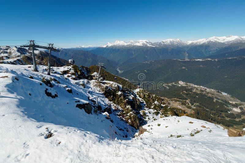 Vista panoramica dalla cima della catena montuosa di Aibga alla stazione sciistica con la teleferica La valle ? circondata dal li fotografie stock