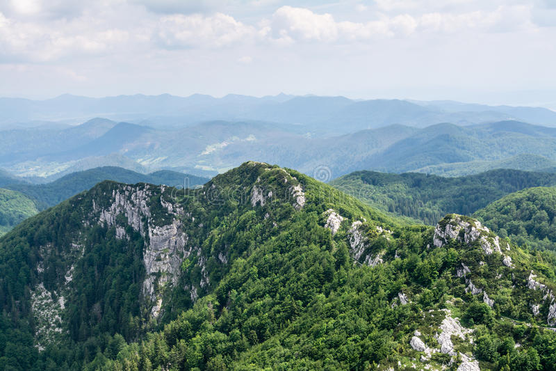 Vista panoramica dalla cima della montagna a molti picchi di montagna intorno fotografia stock