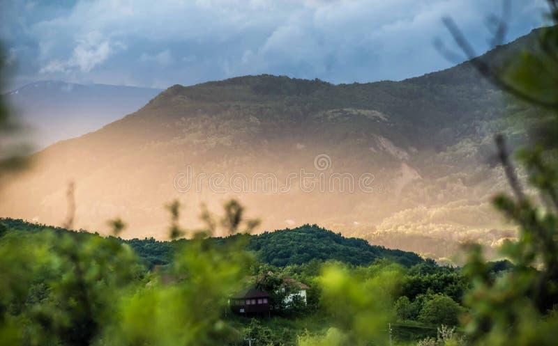 Vista panoramica dei villaggi nella montagna al tramonto ed alla nebbia fotografie stock