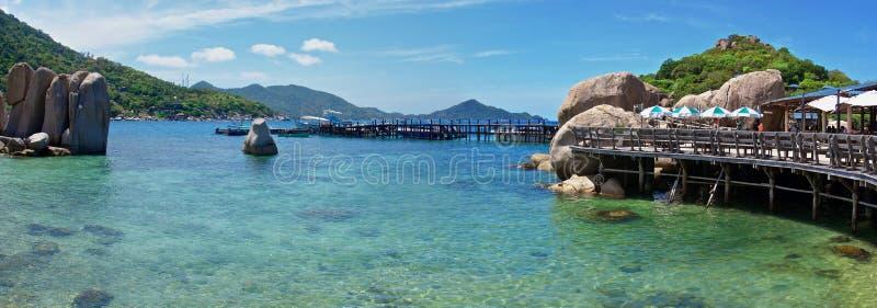 Vista panoramica del pilastro per le barche fra le rocce sulla spiaggia bianca fotografia stock