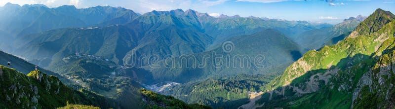 Vista panoramica di estate dalla cima della gamma di Aibga alla stazione sciistica di Rosa Khutor Cabina di funivia ed hotel in u immagini stock libere da diritti