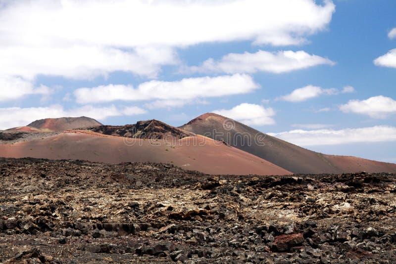 Vista panoramica sopra il giacimento di lava sul cratere e sul cono dei vulcani rossi in Timanfaya NP, Lanzarote, isole Canarie immagine stock