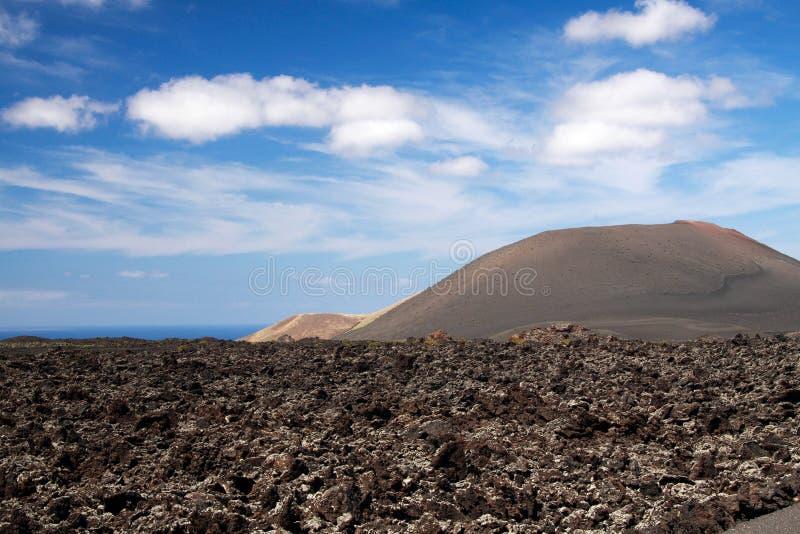 Vista panoramica sopra il giacimento di lava sul cratere e sul cono dei vulcani rossi in Timanfaya NP, Lanzarote, isole Canarie immagini stock