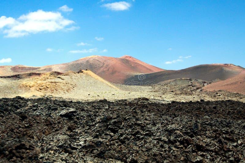 Vista panoramica sopra il giacimento di lava sul cratere e sul cono dei vulcani rossi in Timanfaya NP, Lanzarote, isole Canarie fotografie stock libere da diritti