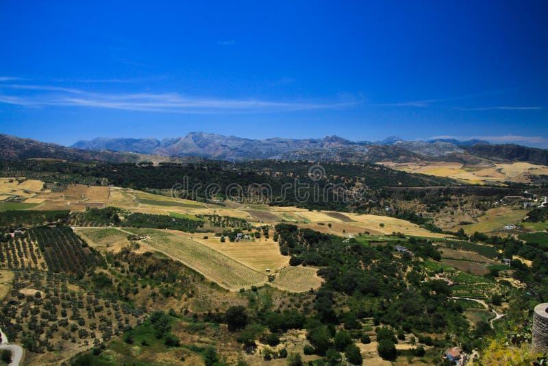 Vista panoramica sopra l'ampia valle rurale che contrappone con il cielo blu senza nuvole dal villaggio antico Ronda - Andalusia, fotografia stock libera da diritti