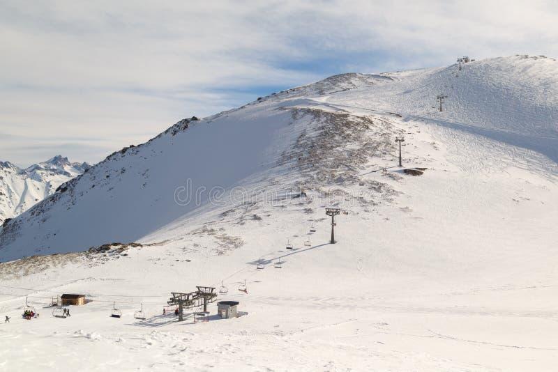 Vista panoramica su una seggiovia e su una montagna nevosa un giorno di inverno soleggiato fotografia stock libera da diritti