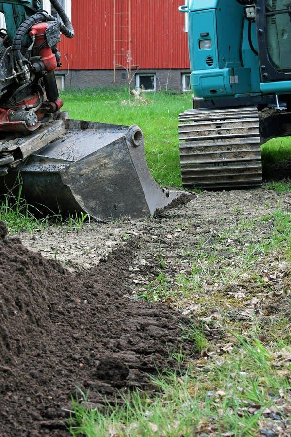 Vista parcial da máquina escavadora, da pá e de uma pilha do solo na jarda fotos de stock