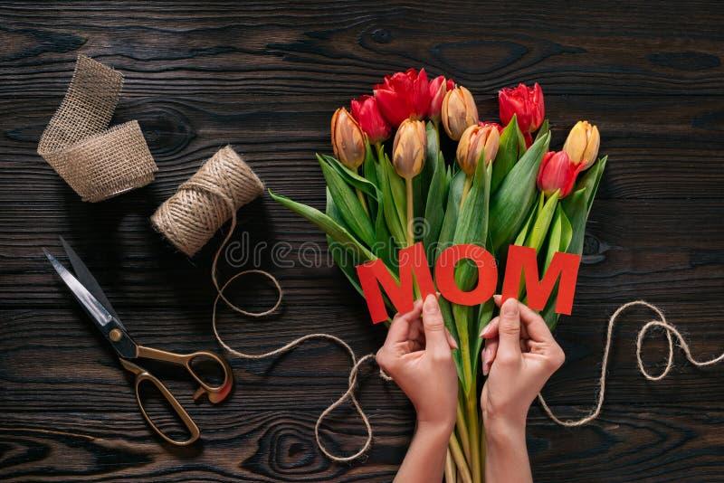 Vista parcial da mulher com rotulação da mamã nas mãos e do ramalhete das tulipas no tabletop de madeira foto de stock
