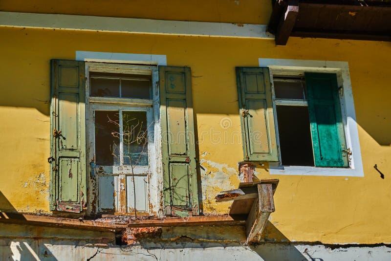 Vista parcial de uma antiga casa destruída com janelas e janelas quebradas e varões e uma sacada quebrada fotos de stock