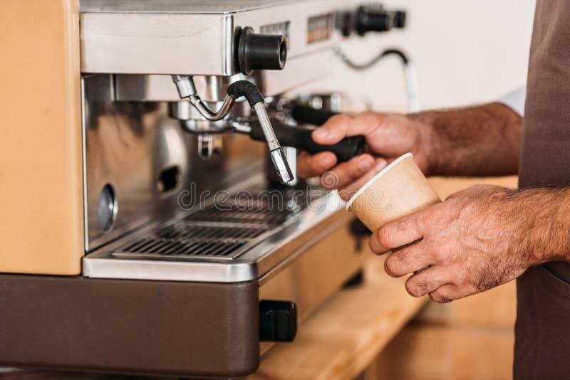 vista parcial del barista usando la máquina del café mientras que fotos de archivo libres de regalías