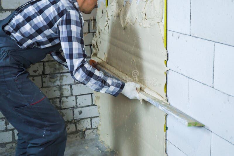 Vista parcial del constructor que enyesa en la pared del bloque fotos de archivo