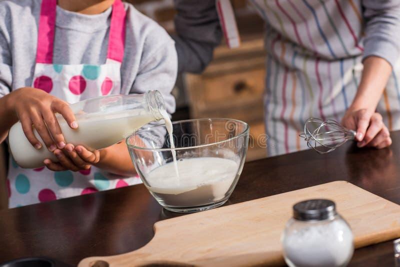 vista parcial do leite de derramamento da menina na bacia ao fazer a massa para cookies junto com a mãe imagem de stock