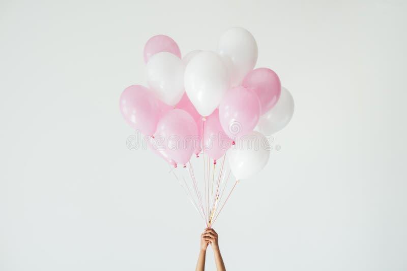 vista parziale delle mani che tengono mazzo di palloni rosa e bianchi immagini stock
