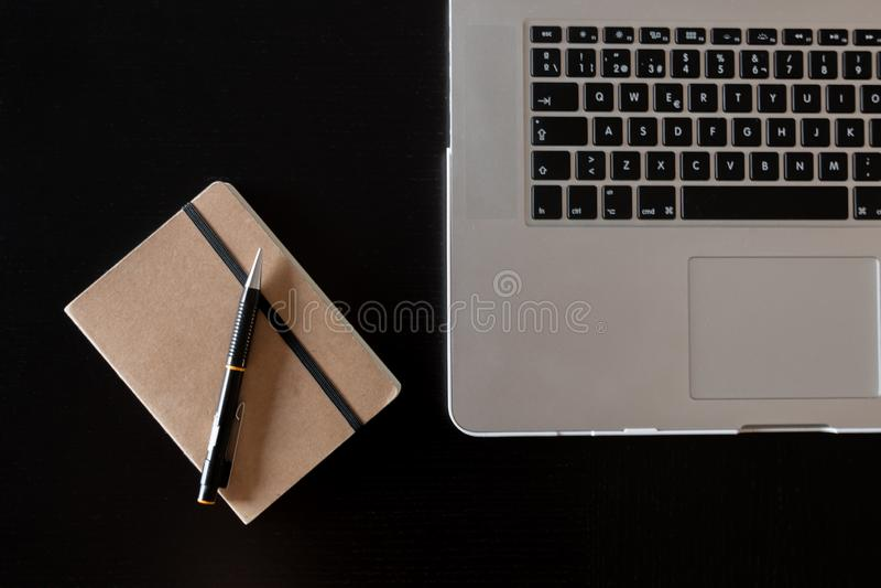Vista parziale di una tastiera d'argento di un computer portatile e di un taccuino con una matita su uno scrittorio di legno scur fotografia stock libera da diritti