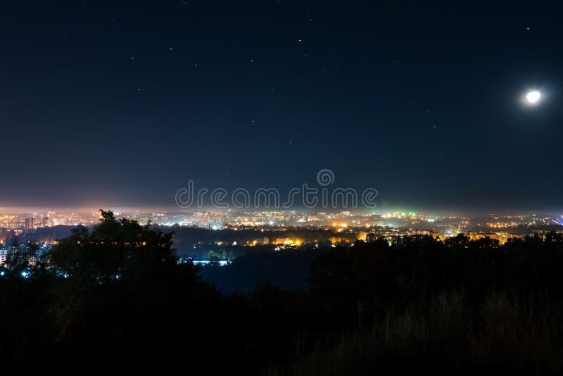 Vista perfecta de una pequeña ciudad de la noche con sus luces de la ciudad, una vista espléndida de la noche luminosa, Khmelnits imagen de archivo
