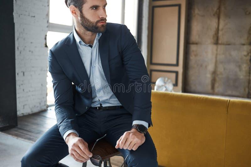 Vista perfeito O homem de negócios farpado atrativo vestido no terno elegante está pensando sobre o negócio e guardar fotos de stock