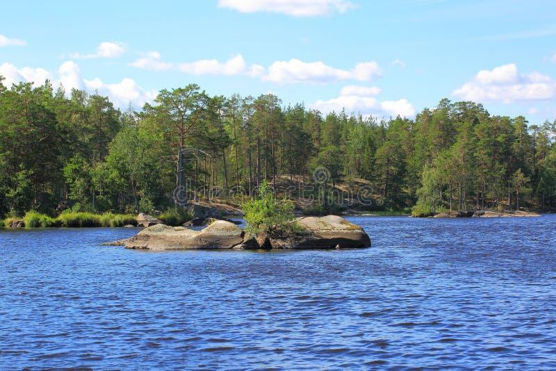 Vista piacevole dell'isola rocciosa in mezzo ad un lago Acqua blu del lago ed alberi verdi su cielo blu con il fondo delle nuvole immagine stock libera da diritti