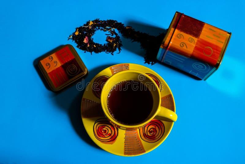 Vista piana del concetto di tempo del t? con la tazza di t? variopinta, contenitore del t?, t? nero sciolto su fondo blu fotografie stock