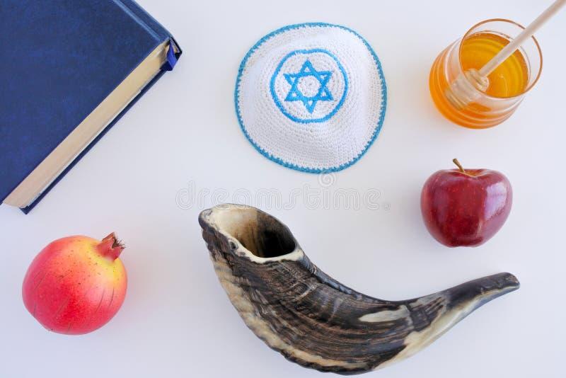 Vista piana di disposizione del libro di Torah, dello Shofar, di Kippa, della mela, del miele e di Pom immagini stock libere da diritti