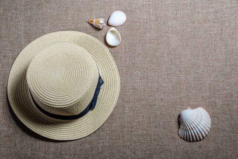 Vista piana di vacanza con il cappello e le conchiglie di paglia fotografia stock libera da diritti