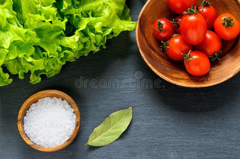 Vista piana superiore degli ingredienti alimentari: lattuga, pomodori, sale per la cottura sul fondo nero della pietra dell'ardes fotografie stock libere da diritti