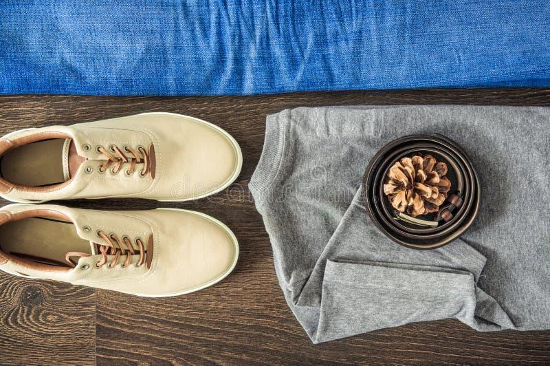 Vista piana superiore di abbigliamento che mette sulla superficie di legno: blue jeans, maglietta grigia, scarpe e cinghia Stile  immagine stock