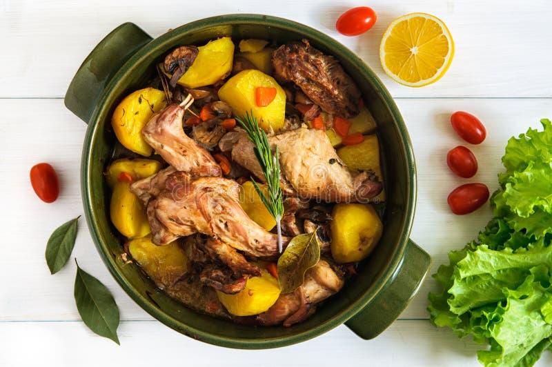 Vista piana superiore di carne di coniglio arrostita con le verdure in vaso ceramico rotondo sulla superficie di legno bianca del fotografia stock