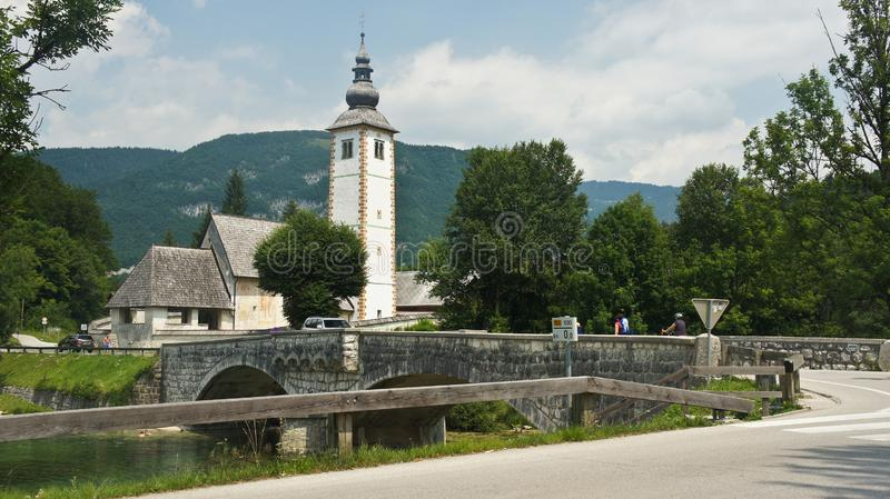 Vista pitoresca da igreja de St John o batista, Julian Alps, ponte e lago, Bohinj, Eslovênia imagem de stock royalty free