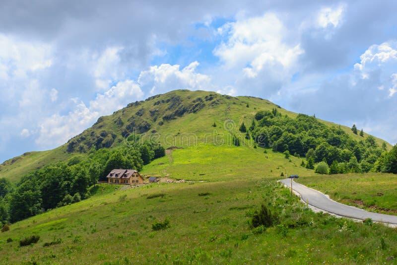 Vista pitoresca do monte verde, do céu azul, da estrada e da casa de campo fotos de stock