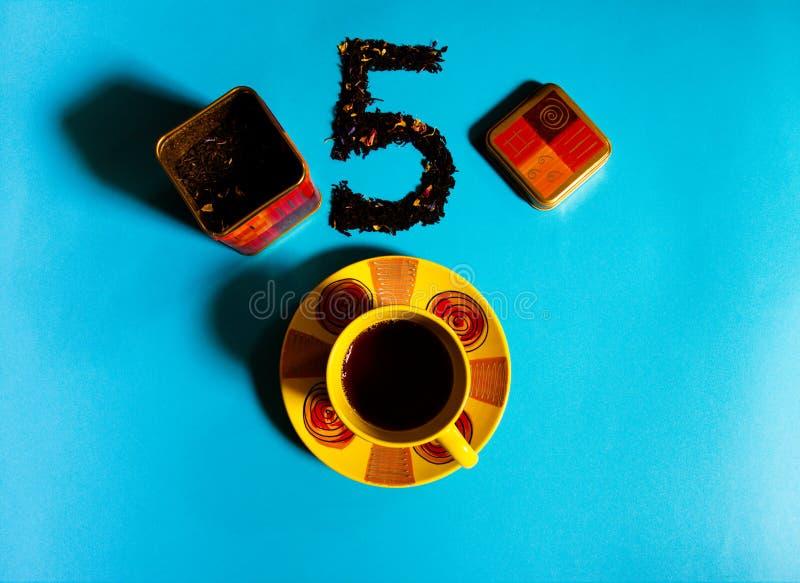 Vista plana del concepto del tiempo del té con la taza de té colorida, envase del té, té negro flojo en fondo azul fotos de archivo libres de regalías