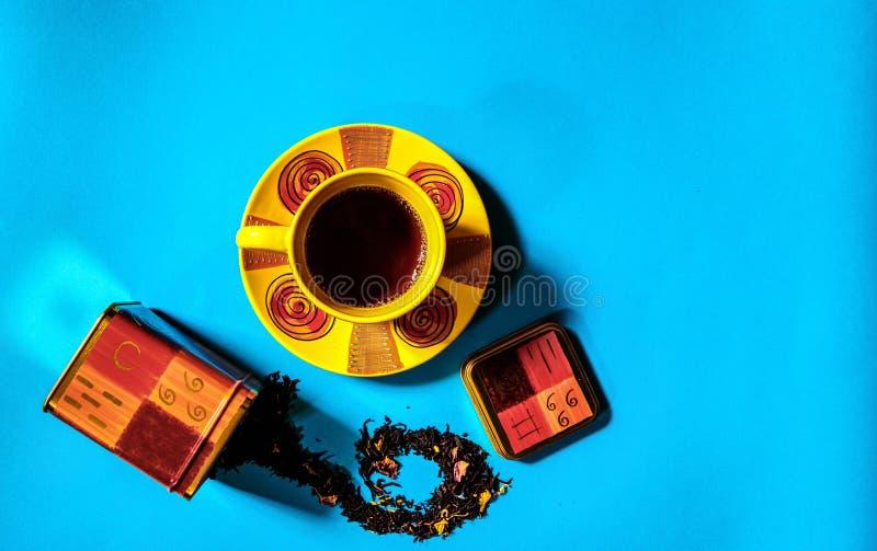Vista plana del concepto del tiempo del té con la taza de té y el envase coloridos del té, té negro flojo en fondo azul con el es imagen de archivo libre de regalías