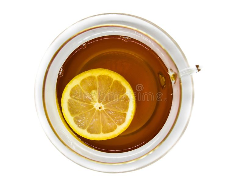 Vista plana del té en taza transparente, de cristal con la rebanada flotante del limón en el fondo blanco foto de archivo