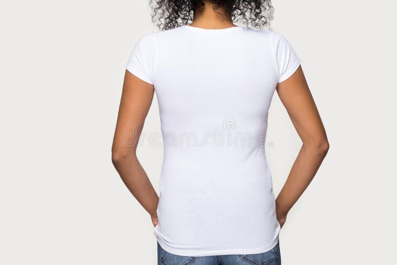 Vista posterior blanca femenina cosechada de la camiseta del africano de la imagen que lleva fotos de archivo libres de regalías