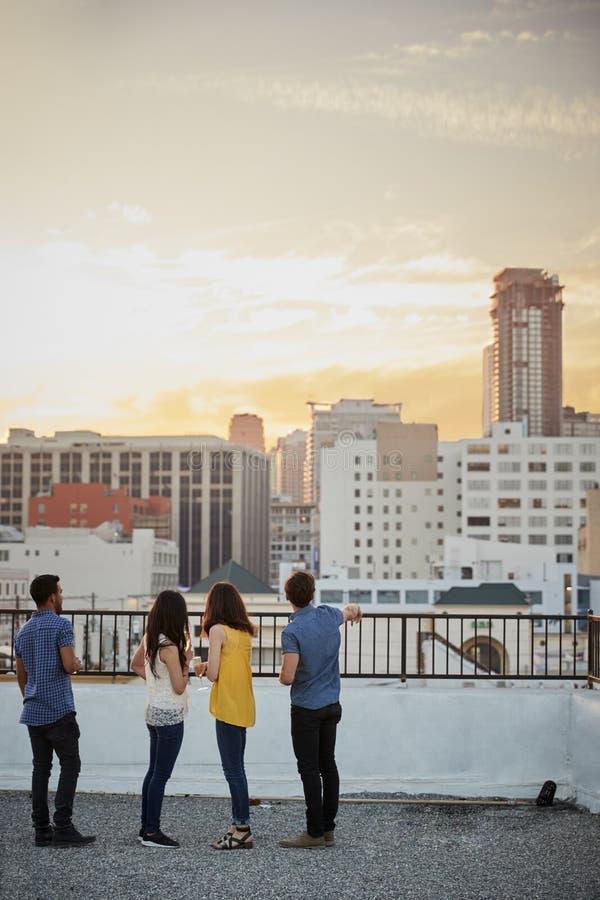 Vista posterior de amigos en la terraza del tejado que considera hacia fuera sobre horizonte de la ciudad la puesta del sol fotos de archivo libres de regalías
