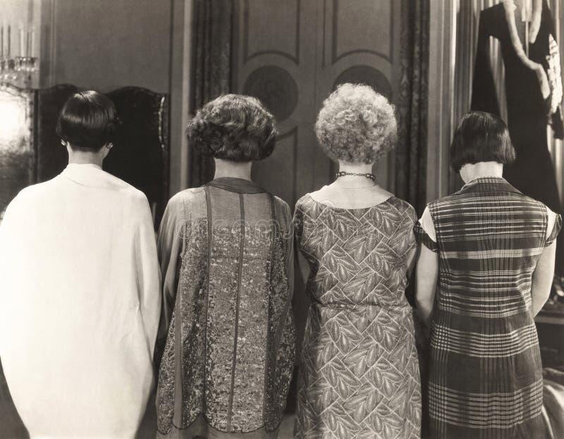 Vista posterior de cuatro mujeres que se colocan en fila imagenes de archivo