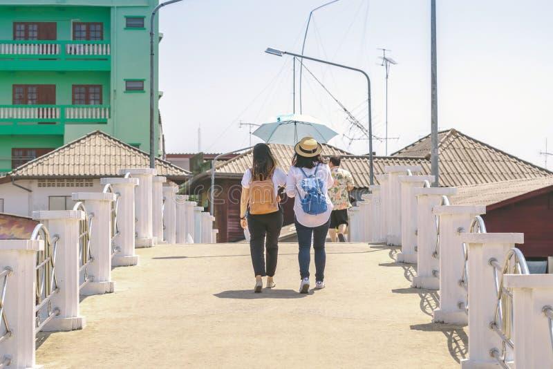 Vista posterior de dos mujeres diseminó un paraguas para bloquear el caliente sol durante el día para caminar por el puente junto foto de archivo